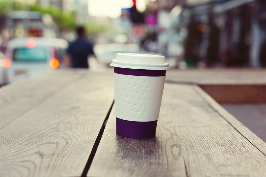 Paper coffee cup on wooden table over bokeh street
