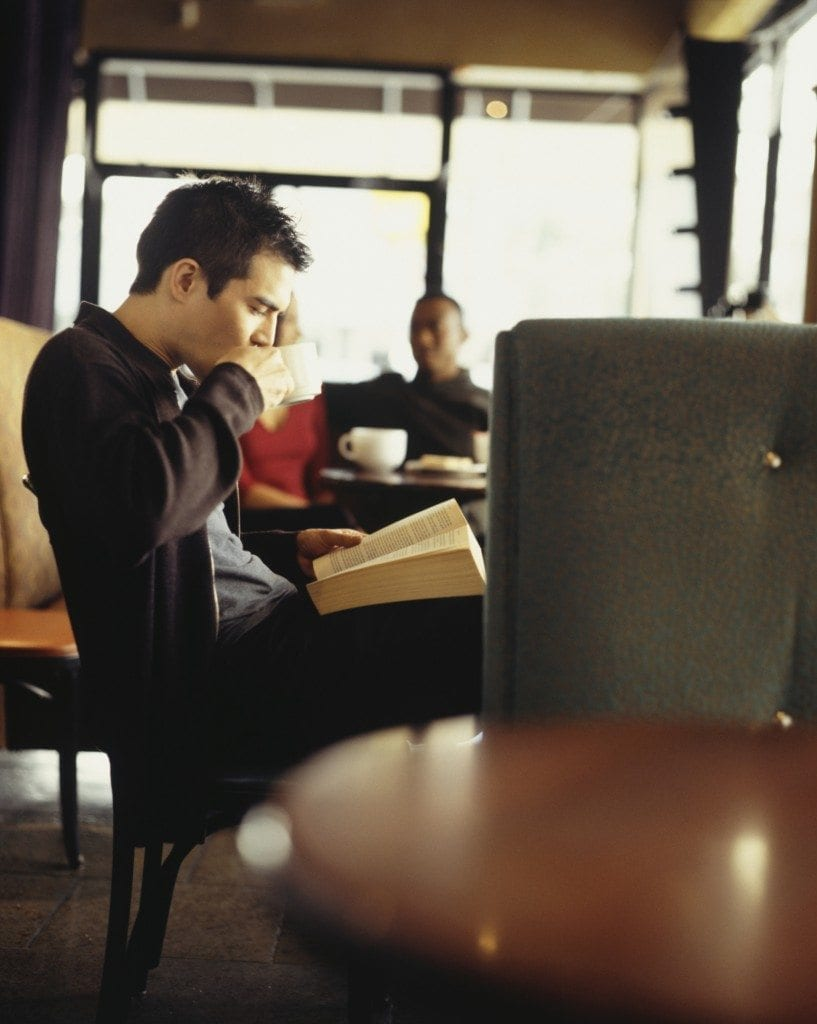 Young man reading book in coffee shop