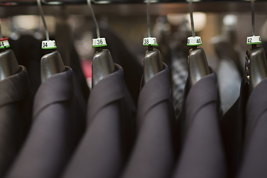 Close-up of business suits hanging in clothing store.