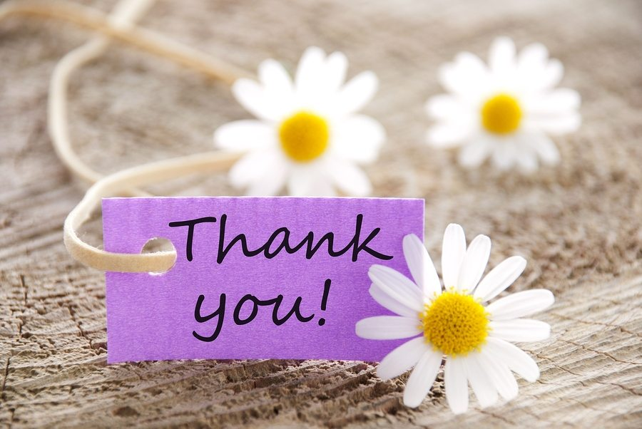 a purple label with Thank you on it and flowers in the background ** Note: Slight blurriness, best at smaller sizes