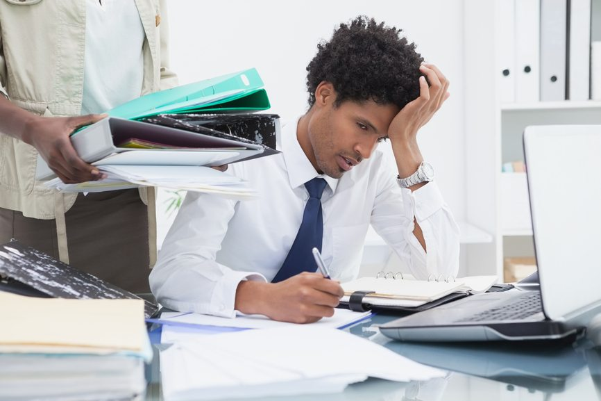 Woman giving pile of ring binders to her exhausted colleague in the office